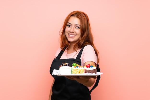 Het roodharigemeisje dat van de tiener veel verschillende minicakes over geïsoleerd roze met gelukkige uitdrukking houdt