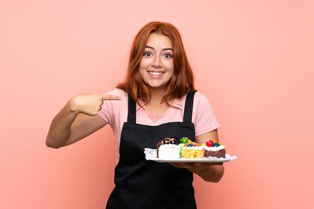 Het roodharigemeisje dat van de tiener veel verschillende minicakes over geïsoleerde roze achtergrond met verrassingsgelaatsuitdrukking houdt