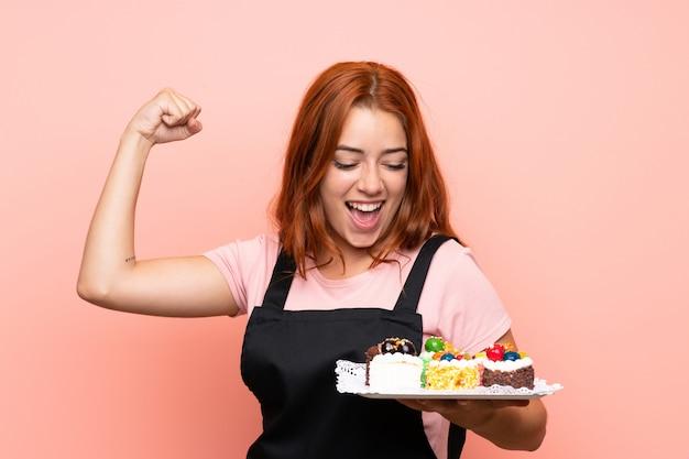 Het roodharigemeisje dat van de tiener veel verschillende minicakes over geïsoleerde roze muur houdt die een overwinning viert