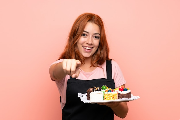 Het roodharigemeisje dat van de tiener veel verschillende minicakes over geïsoleerde roze muur houdt richt vinger op u met een zekere uitdrukking