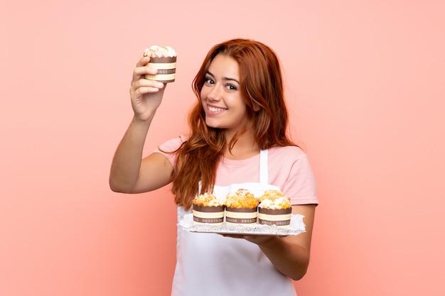 Het roodharigemeisje dat van de tiener veel verschillende minicakes over geïsoleerdo houdt