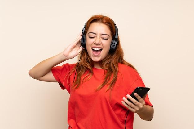 Het roodharigemeisje van de tiener het luisteren muziek met mobiel over geïsoleerd
