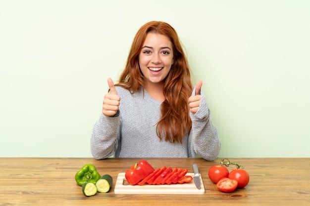 Het roodharigemeisje van de tiener met groenten in lijst geven duimen op gebaar