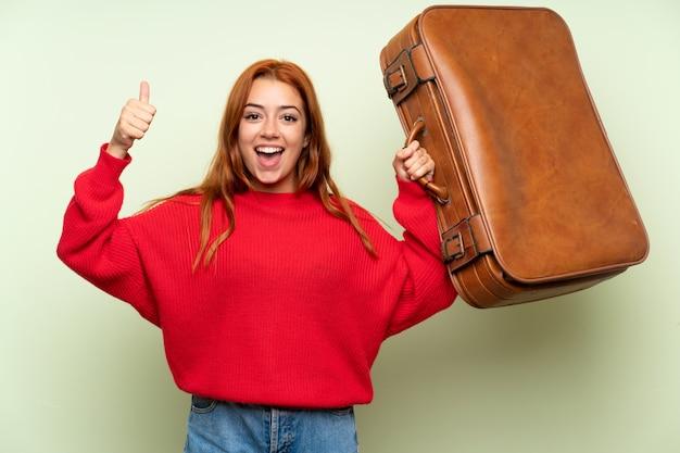 Het roodharigemeisje van de tiener met sweater die een uitstekende aktentas houdt