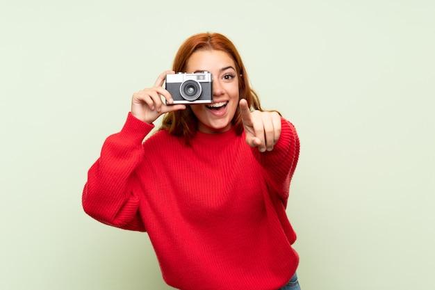 Het roodharigemeisje van de tiener met sweater over geïsoleerde groen houdend een camera