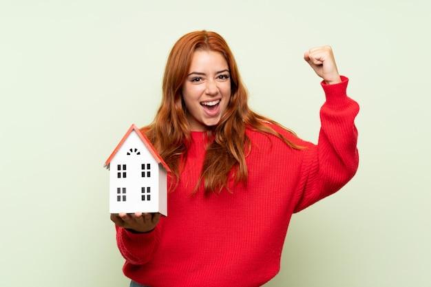 Het roodharigemeisje van de tiener met sweater over geïsoleerde groen houdend een klein huis