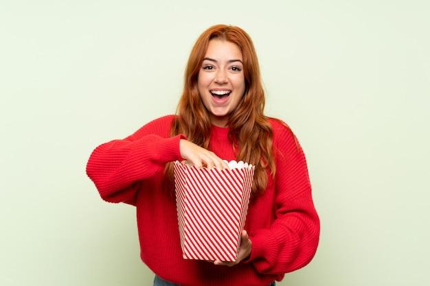 Het roodharigemeisje van de tiener met sweater over geïsoleerde groen houdend een kom popcorns