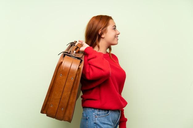 Het roodharigemeisje van de tiener met sweater over geïsoleerde groen houdend een uitstekende aktentas