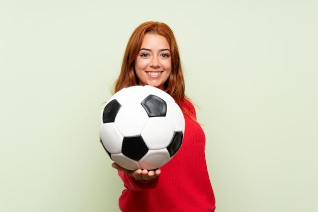 Het roodharigemeisje van de tiener met sweater over geïsoleerde groen houdend een voetbalbal