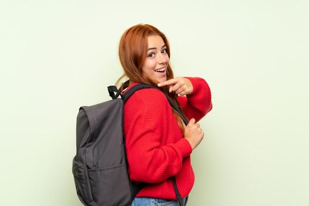 Het roodharigemeisje van de tiener met sweater over geïsoleerde groene achtergrond met rugzak