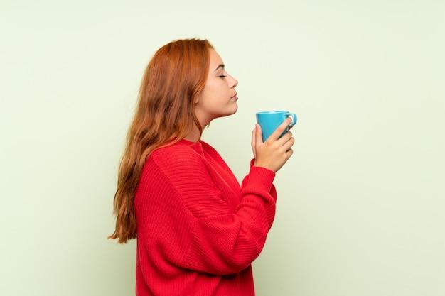 Het roodharigemeisje van de tiener met sweater over geïsoleerde groene holdings hete kop van koffie