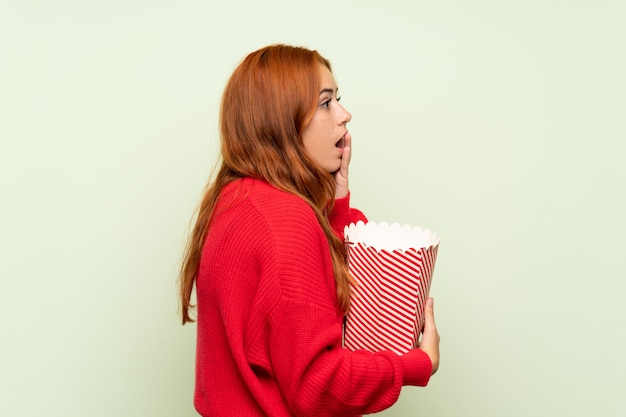 Het roodharigemeisje van de tiener met sweater over geïsoleerde groene muur die een kom popcorns houdt