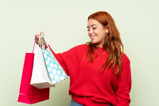 Het roodharigemeisje van de tiener met sweater over geïsoleerde groene muur die heel wat het winkelen zakken houdt