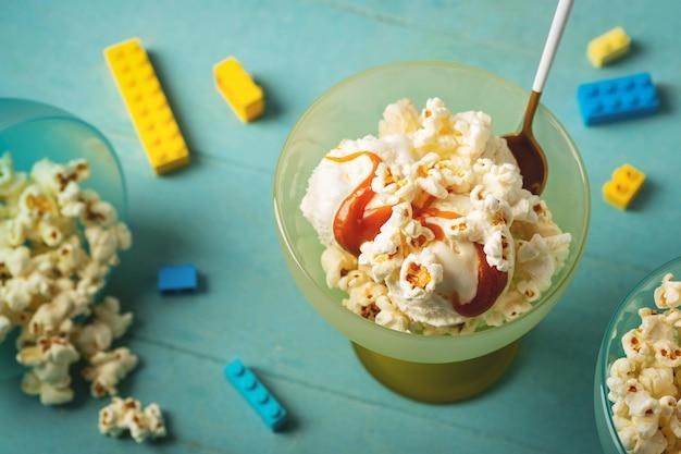 Het roomijs met karamel en popcorn, blauwe achtergrond, kinderen behandelt dessertconcept