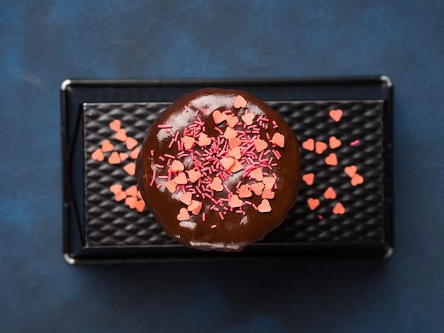 Het roomkaasbiscuitgebak met chocoladeglans en het roze hart bestrooit op donkerblauwe achtergrond.