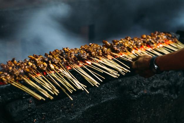 Het roosteren van vlees, kip en schapenvlees satays met houtskool, vuur en rook.