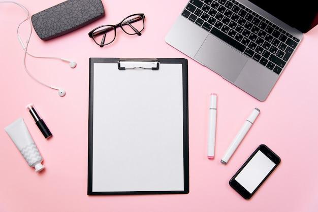 Het roze bureau van vrouwen met schoon blad van document met vrije exemplaarruimte, laptop, telefoon met het lege witte scherm, een room, lippenstift, hoofdtelefoons, oogglazen en leveringsachtergrond.