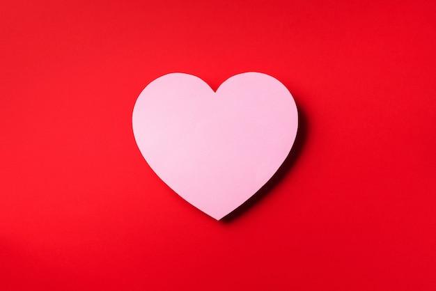 Het roze hart sneed van document over rode achtergrond met exemplaarruimte. valentijnsdag. liefde, datum, romantisch concept.