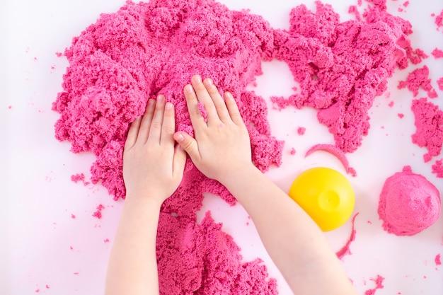 Het roze magische zand in jonge geitjes overhandigt dicht omhoog op een witte ruimte. vroeg zintuiglijk onderwijs. voorbereiden op school. ontwikkeling