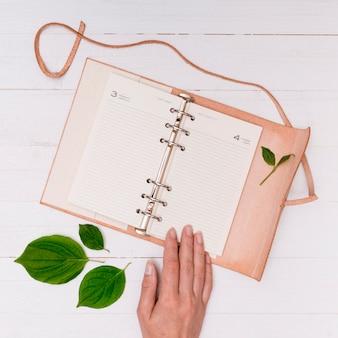 Het roze notitieboekje van de close-up met hand