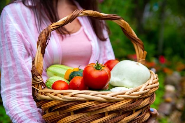 Het ruikt naar vers geplukte groenten. boer met mand met oogst uit moestuin