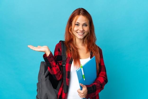 Het russische meisje van de tienerstudent op blauwe denkbeeldige holding copyspace op de palm om een advertentie en met omhoog duimen op te nemen