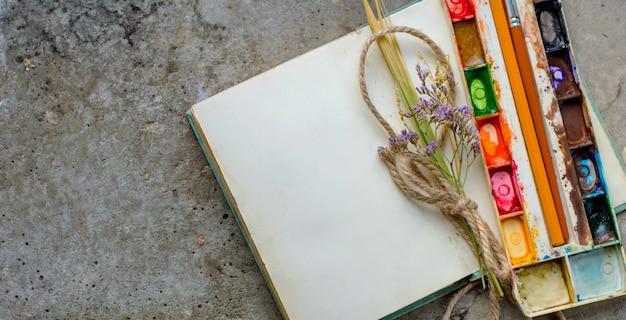 Het rustieke uitstekende notaboek op concrete grond met vlakke waterverfverven, legt, copyspace