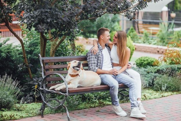 Het rustmoment! mooi glimlachend paar met hun hond in het park op een zonnige dag