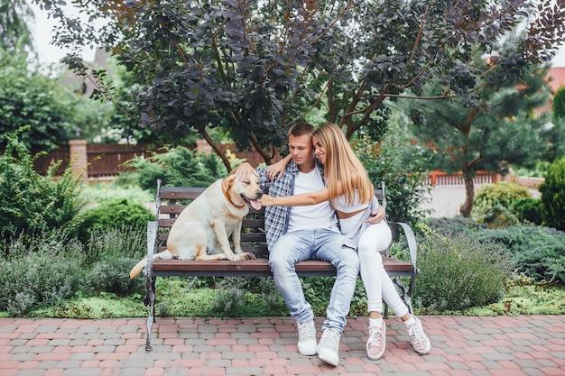 Het rustmoment! mooi paar met hun hond in het park op een zonnige dag. jonge familie die labrador aait en op de bank zit.