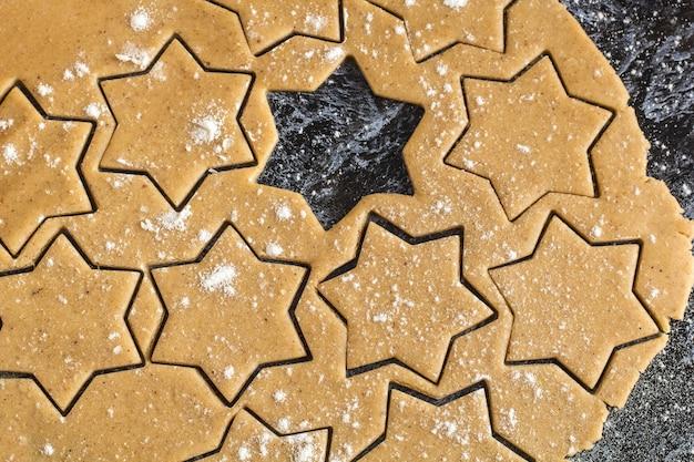 Het ruwe deeg van de kerstmis eigengemaakte peperkoek uitgerold op donkere lijst