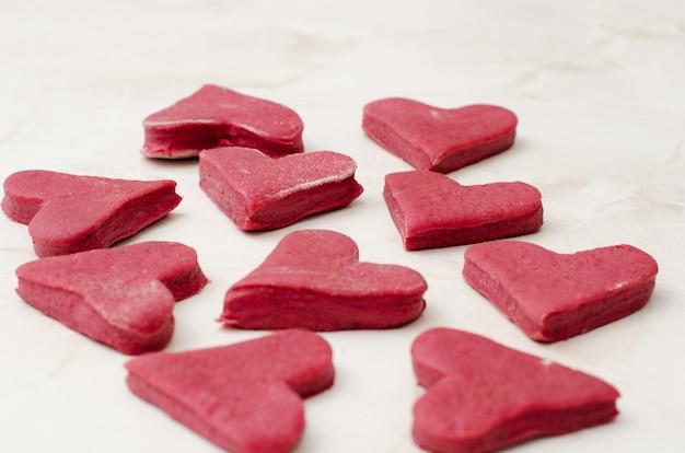 Het ruwe hart van het koekjesdeeg van biet op een witte lijst
