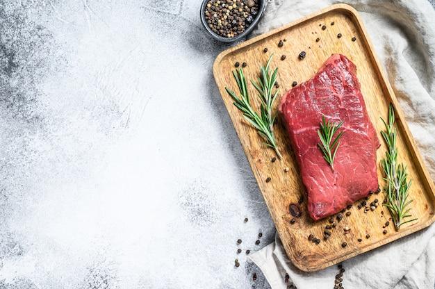 Het ruwe lapje vlees van het strooklendestuk op een houten dienblad. rund vlees. bovenaanzicht copyspace-achtergrond