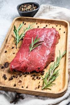 Het ruwe lapje vlees van het strooklendestuk op een houten dienblad. rund vlees. bovenaanzicht