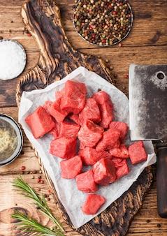 Het ruwe magere in blokjes gesneden varkensvleeslapje vlees van het braadpanrundvlees op hakbord met uitstekende vleesbijlen. zout en peper