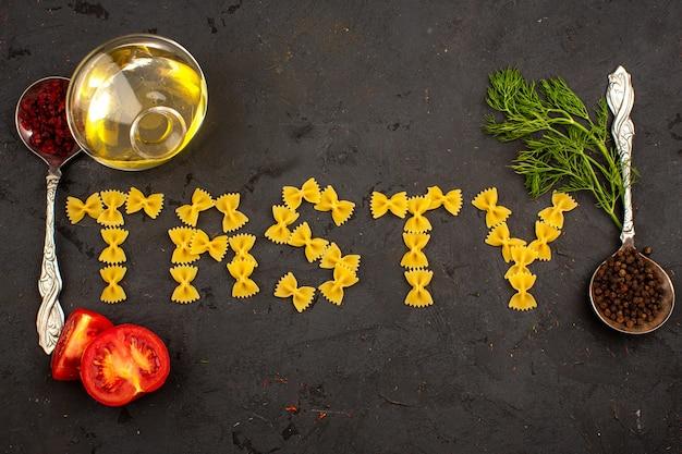 Het ruwe smakelijke woord van deegwaren gevormd met olie rode gesneden tomaten en greens die op een donkere vloer omringen