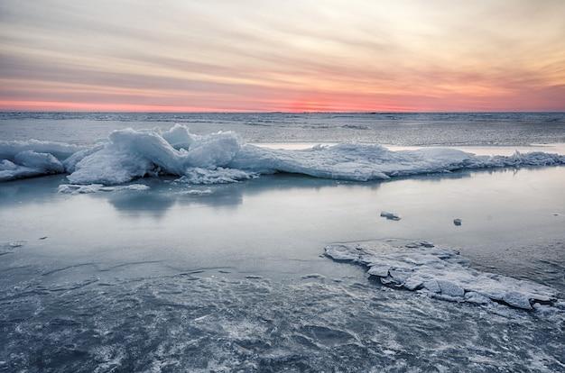 Het samenvatting bevroren zeegezicht van de de winterzonsopgang met ijs en kleurde de hemel.