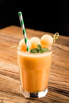 Het sap van meloen met munt in een glas op tafel.hami meloen