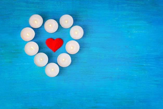 Het scharlaken hart is omgeven door brandende kleine hartvormige kaarsjes op een blauwe houten achtergrond.