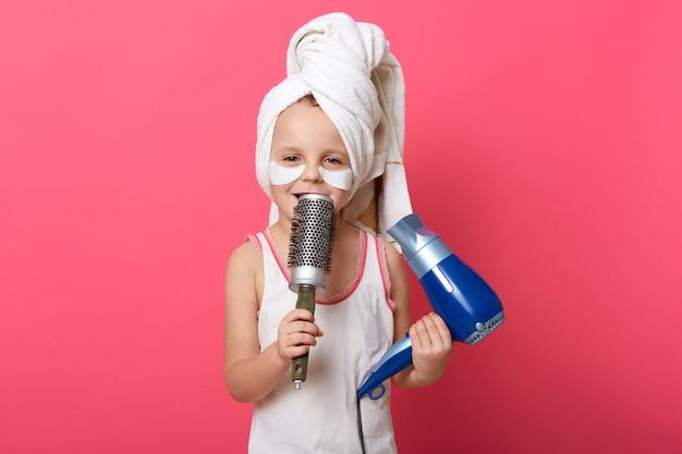 Het schattige kind stelt zich voor dat ze een superster is en zingt met een kam in handen