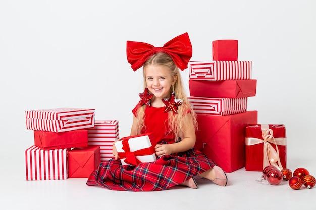 Het schattige kleine meisje wordt overwogen voor kerstmis. witte achtergrond, grote geschenkdozen, ruimte voor tekst. het concept van kerstmis