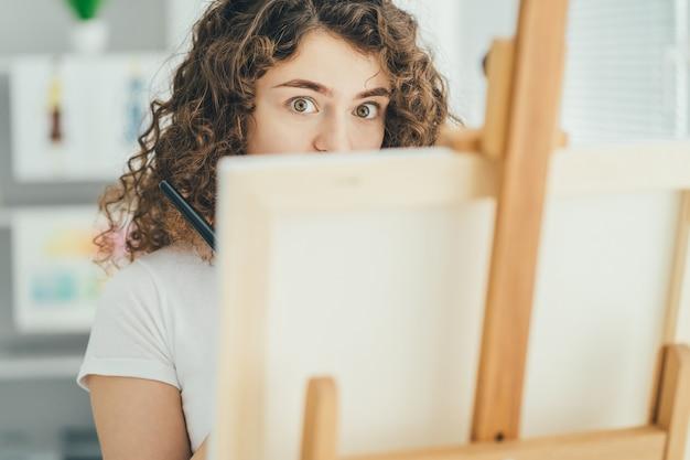Het schattige meisje dat een foto schildert op de ezel