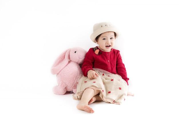Het schattige meisje in een hoed en rode jurk op wit