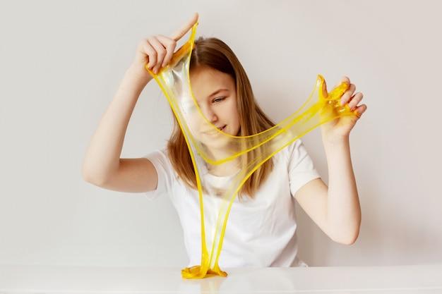 Het schattige meisje lacht en speelt met het gele slijm