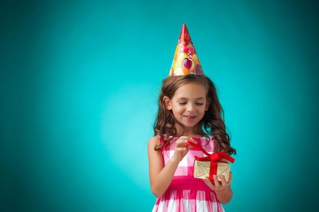 Het schattige vrolijke kleine meisje op blauwe achtergrond