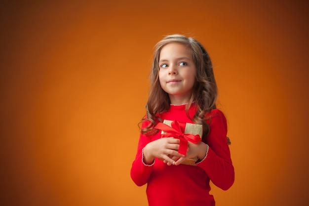 Het schattige vrolijke kleine meisje op een oranje achtergrond