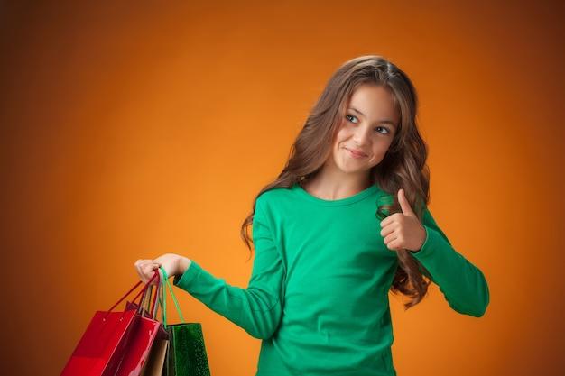 Het schattige vrolijke meisje met boodschappentassen op een oranje achtergrond