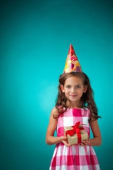 Het schattige vrolijke meisje met feest hoed op blauwe muur