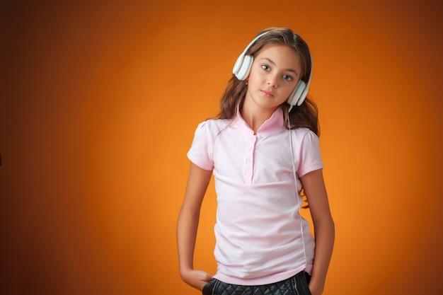 Het schattige vrolijke meisje met koptelefoon op oranje muur