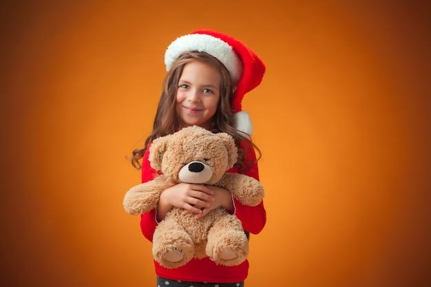 Het schattige vrolijke meisje met teddybeer op oranje achtergrond
