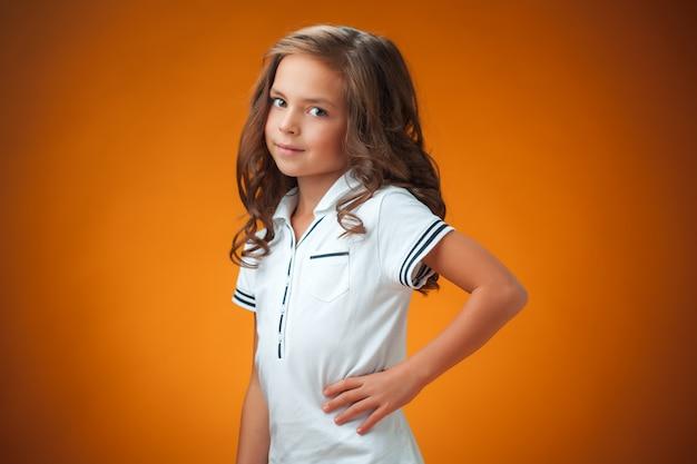 Het schattige vrolijke meisje op oranje achtergrond